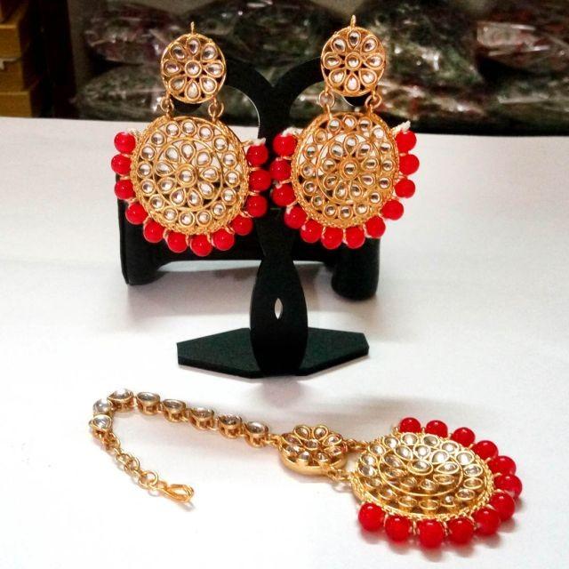 conjunto de pendientes rojos con joya frente